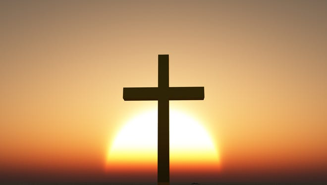 A sunrise, or sunset, is shown behind a cross.