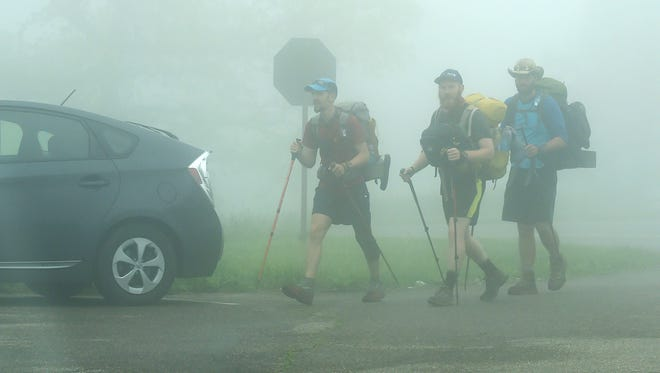"Hiking the Appalachian Trail, Ben ""Goose"" Mitchell of Tennessee, David ""Ribbit"" Blount of George and Nick ""Shrink"" Hart of Florida step out of the fog as they arrive at the point where the Skyline Drive meets the Blue Ridge Parkway on top of Afton Mountain on a foggy Thursday morning, May 12, 2016."