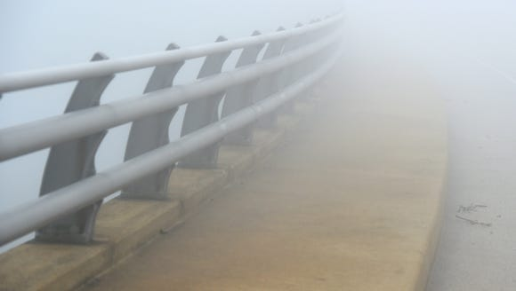 The railing and sidewalk disappears into the fog as
