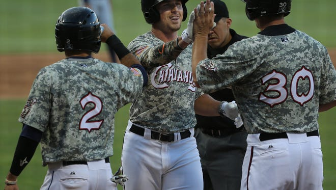 El Paso's Hunter Renfroe receives congratulations from teammates Carlos Asuaje, left, and Alex Dickerson after Renfroe hit a drive over the right centerfield wall Monday. Dickerson has also homered earlier.