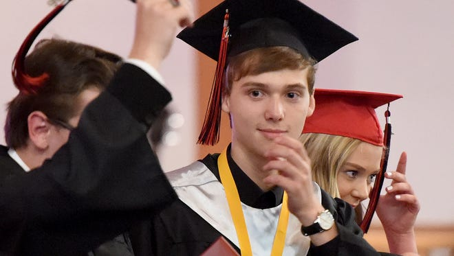 Graduate and valedictorian Colin Daniel Jones moves to toss his cap into the air after turning his tassel during commencement exercises for Ridgeview Christian School in Stuarts Draft on Friday, May 27, 2016.