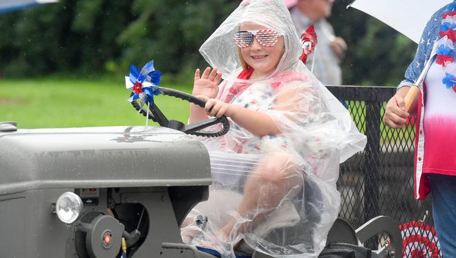 A girl pretends to drive a tractor, which is on a trailer being pulled in the parade, as she waves to the crowd. America's Birthday Celebration held its annual parade in Gypsy Hill Park on Monday, July 4, 2016.