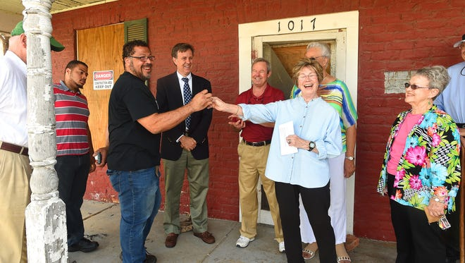 Mark Holmes receives symbolic keys of ownership from Velma Ryan, president of Red Brick House Inc., a group that fought to save the house. The organization hosted a ceremony on the porch of the 19th-century red brick Arnold House to recognize transfer of ownership of the building to Holmes, owner of a counteracting company named The Wood Bore. The ceremony took place at the house located on New Hope Road in Waynesboro on Friday morning, July 8, 2016.