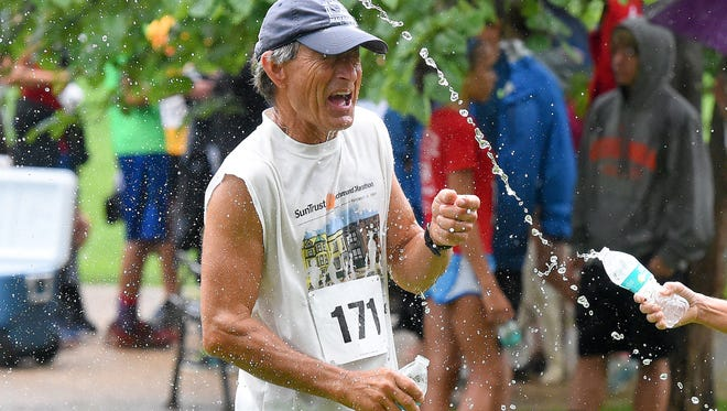 Harry Crosby reacts as he gets doused with water by Bev Crosby after both complete the Firecracker 5K in Gypsy Hill Park on Monday, July 4, 2016.