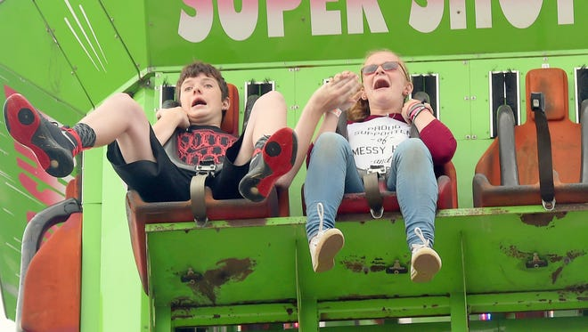 Thirteen-year-olds Camdem Clements and Briana Hatter of Weyers Cave react to the sudden drop as they ride the Super Shot on the midway during the second day of the Augusta County Fair on Wednesday, August 3, 2016. The fair continues through Saturday.