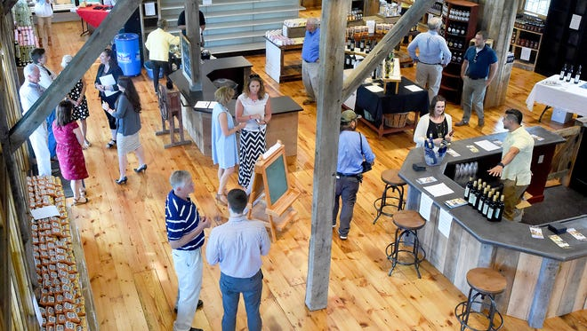 Those gathered mingle and explore inside the soon to open Valley Pike Farm Market. A preview event allowed for an early glance of the market, which will be home to several local shops, on U.S. 11 in Weyers Cave on Thursday, Aug. 4, 2016.