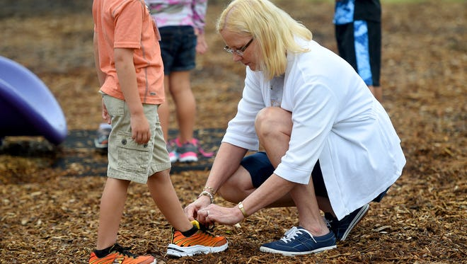 First grade teacher Sherry Liggett ties the shoelace of one of her students during recess on the first day of school Tuesday, Aug. 9, 2016 at Beverley Manor Elementary.