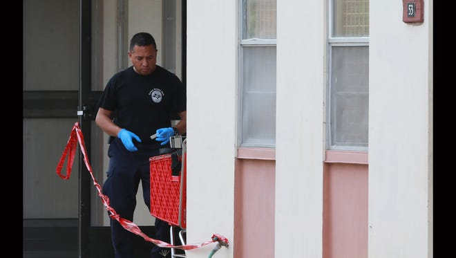 """An El Paso Police Department crime scene officer works Tuesday at an apartment where police said the body of Eric Tijerina, 36, was found with """"obvious signs of foul play"""" Monday at the Rio Grande Apartments, 212 Lisbon St."""