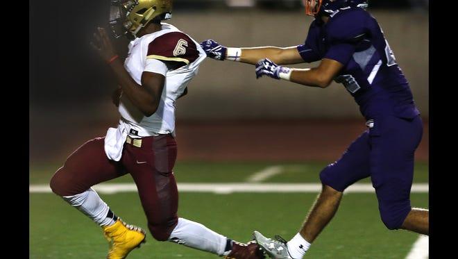 El Dorado quarterback Cedarious Barfield runs out of the grasp of Eastlake defender Andres Carmona to score a long touchdown during third quarter action Friday.