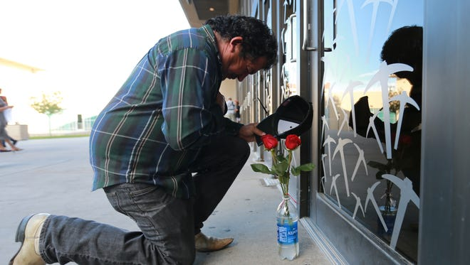 Juan Ortiz bowed in prayer after leaving roses at the door of the Don Haskins Center where Juan Gabriel was to have played Sunday evening. Ortiz said he is a lifelong fan.