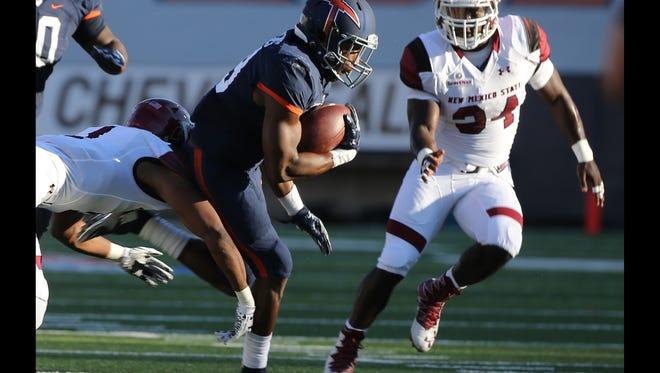 UTEP's Aaron Jones breaks between NMSU defenders to score the game's first touchdown Saturday.