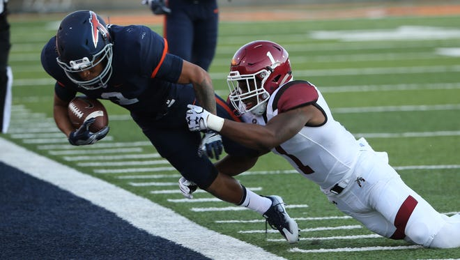 "UTEP's Terry Juniel is pushed out of bounds  by NMSU""s Jacob Nwangwa after a reception Saturday."