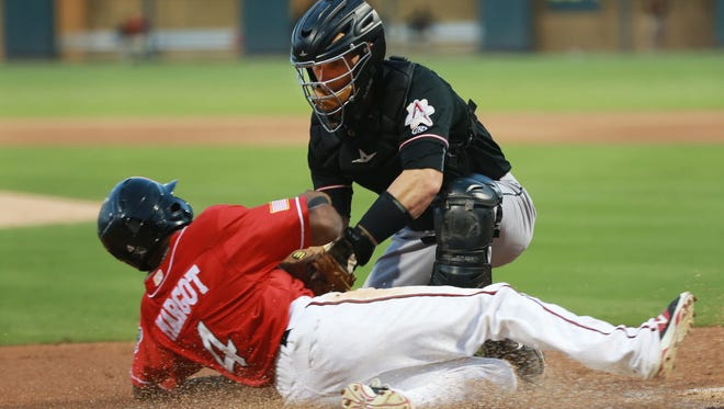 Albuquerque catcher Dustin Garneau tags out El Paso's Manuel Margot out at home plate on a double steal attempt Sunday.