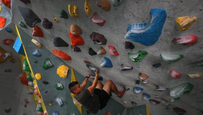 Gerardo Gonzalez climbs a wall Saturday at Cave Climbing Gym.