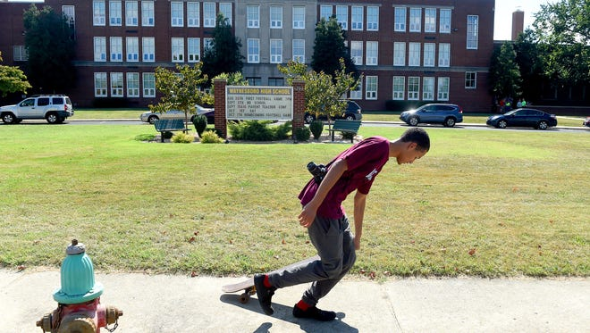 Camera slung over his shoulder, junior Isaiah Holloway sets his skateboard into motion and prepares to jump on. He uses it to get around on the sidewalks out front of Waynesboro High School while photographing the school during photography class on Tuesday, Sept. 13, 2016.