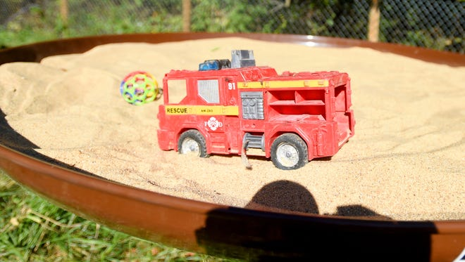 A toy firetruck is stuck in the sand of an elevated sandbox located in the area set aside for the natural play area being developed at Montgomery Hall Park in Staunton on Tuesday, Sept. 13, 2016.