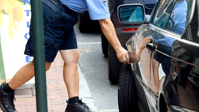 """Parking enforcement officer Mary Fitzgerald chalks the tires of vehicles parked along West Beverley Street. She goes about her job with the Staunton Police Department  on Thursday, Sept. 15, 2016. """"I've been at this for 21 years,"""" she says about her time in parking enforcement."""