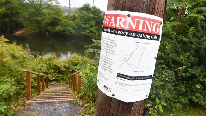 A posted sign near steps leading down to the river offers a warning along with information on a health advisory on eating fish caught in the South River near Constitution Park in Waynesboro on Wednesday, Sept. 28, 2016.
