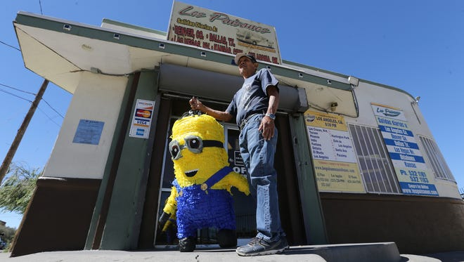 Juan Vega carries a Minion piñata to a bus station on Montestruc Court near the entrance to Chihuahuita on Tuesday.