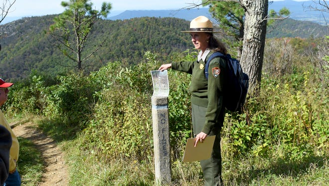 Sally Hurlbert, a public affairs officer with the National Park Service, holds a photo of the same spot to show how vegetation at the location went from having been burned away to what is visible along a trail in the Shenandoah National Park, just off the Skyline Drive on Tuesday, Oct. 11, 2016. The trail was among the more than 10,000 acres which burned as part of the Rocky Mountain fire which burned six months ago.