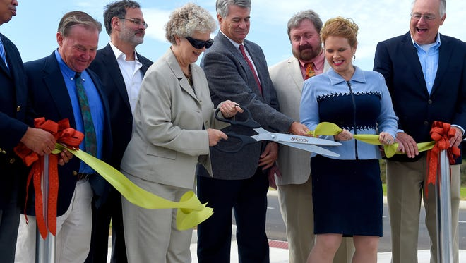 Mayor Carolyn Dull of Staunton uses the big scissors to cut the ribbon as other members of the city council and participants in the project help pull the ribbon apart after it proved stubborn. They participate in a ground breaking ceremony for Staunton Crossing on Thursday morning, Oct. 13, 2016.