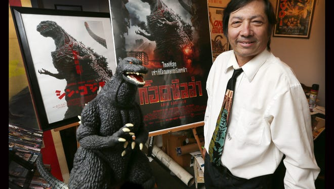 "David Nuñez is a collector of Godzilla movie posters. The posters behind him are from the movie ""Shin Godzilla."""