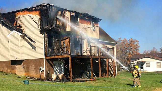 Smoke rises from the structure as firefighters work to battle a working residential fire at 1016 Cold Springs Road near Stuarts Draft on Thursday, Nov. 17, 2016.