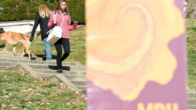 A senior at the school, Dallana Alvarez follows the steps down hill carrying a beverage in either hand while on the campus of Mary Baldwin University on Thursday, Dec. 1, 2016.