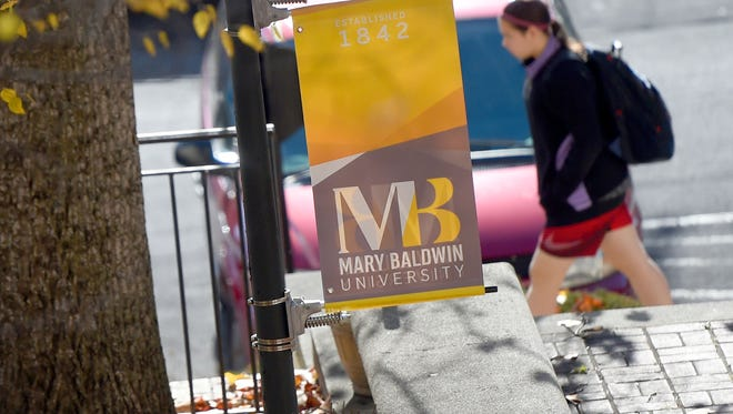A walks past a banner displayed on the campus of Mary Baldwin University.