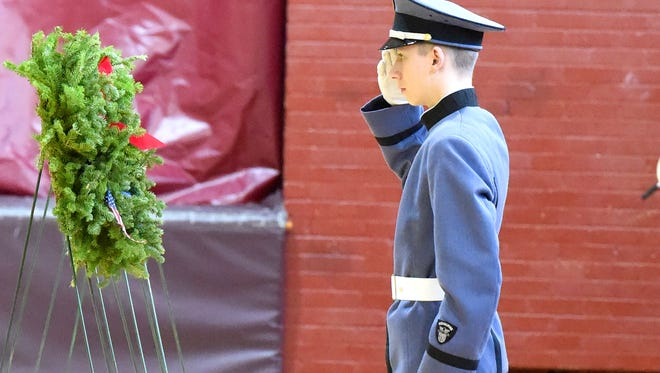 A cadet offers a salute after placing one of several wreaths honoring veterans during the Wreaths Across America ceremony held at Fishburne Military School on Tuesday, Dec. 13, 2016.