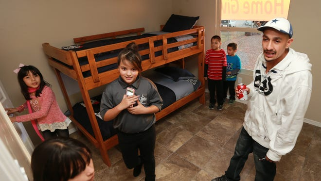 The Elias family inspected a bedroom in their new home Wednesday. The family includes (clockwise from right) father Osvaldo Elias, Sr., Dalilah Elias, 10, Mariah Elias, 9, Osvaldo Elias, Jr., 8 and Angel Elias, 5. Cousin Sarah Juarez is at center.