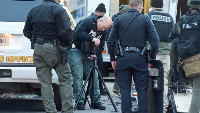 Officers with Staunton Police Department pack up their gear after a suspect, wanted by the Augusta County Sheriff's Office, surrenders at a house on Gay Street in Staunton on Wednesday, Dec. 21, 2016.