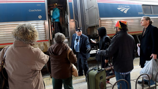 Conductor R.S. Glass helps travelers with boarding Amtrak's eastbound Cardinal #50 train before it departs the train station in Staunton on one of their largest travel days of the year on Friday, Dec. 23, 2016.