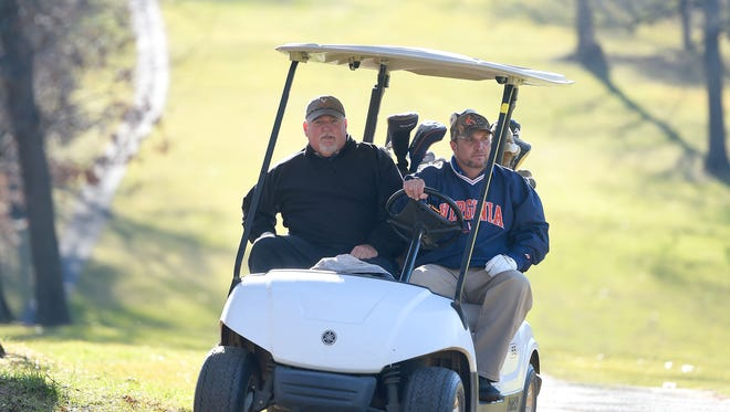 Scott Fitzgerald (right) of Staunton drives the golf cart that carries he and Steven King of Waynesboro towards the ninth hole on the golf course at Gypsy Hill Park on Wednesday, Dec. 28, 2016.