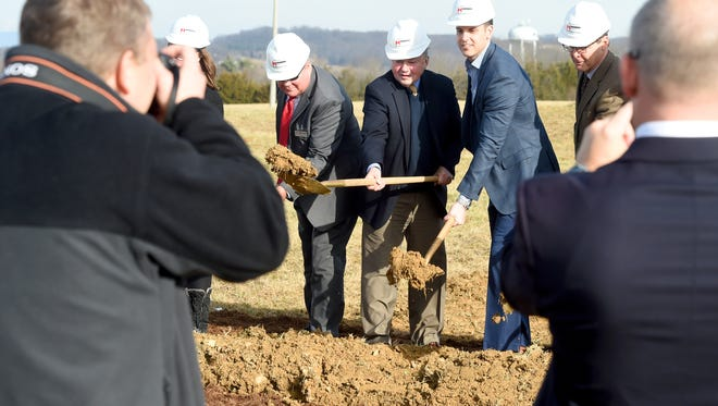 Hard hats on and golden shovels in hand, participants strike a pose for the cameras as part of a symbolic groundbreaking for a new 108,000 square-foot facility being built by InterChange Group Inc during a ceremony at Mill Place Commerce Park in Verona on Thursday, Jan. 12, 2017.