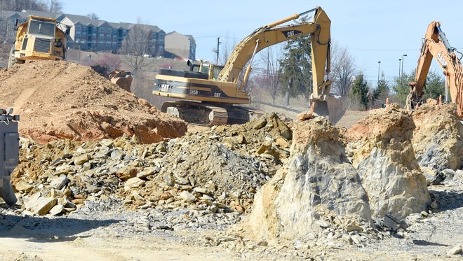 An excavator loads dump moves earth as it waits for another dump truck to arrive and be filled. Construction continues on land designated for the Frontier Center project, alongside the road that leads to the entrance of the Frontier Culture Museum in Staunton on Monday, Feb. 20, 2017.