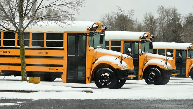 School buses are parked in the snow in the Kmart parking lot in Waynesboro on Monday, March 14, 2017.