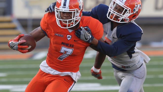 UTEP receiver Kavika Johnson tries to shake a tackle after making a short reception Friday.