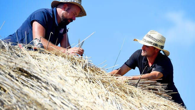 Mike Tripp/The News Leader Luke Robinson and Greg Harrison of McGhee & Co. Roof Thatchers work together to place, trim and dress the the bundle of reeds just placed. They work as part of the team re-thatching the roof of the farmhouse on the 1700s Irish farm at the Frontier Culture Museum on Thursday. The building's previous thatch roof originally burned in a fire, started by a spark from the chimney, on April 5. Luke Robinson and Greg Harrison of McGhee & Co. Roof Thatchers work together to place, trim and dress the the bundle of reeds just placed. They work as part of the team re-thatching the roof of the farmhouse on the 1700s Irish farm at the Frontier Culture Museum on Thursday, June 16, 2016. The building's previous thatch roof originally burned in a fire, started by a spark from the chimney, on April 5.