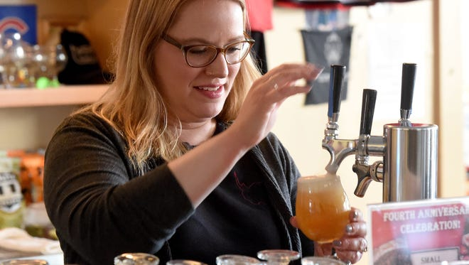 Taproom manager Amanda Mace pours beer from the taps for the customers at Redbeard Brewing Co. in downtown Staunton on April 14, 2017.
