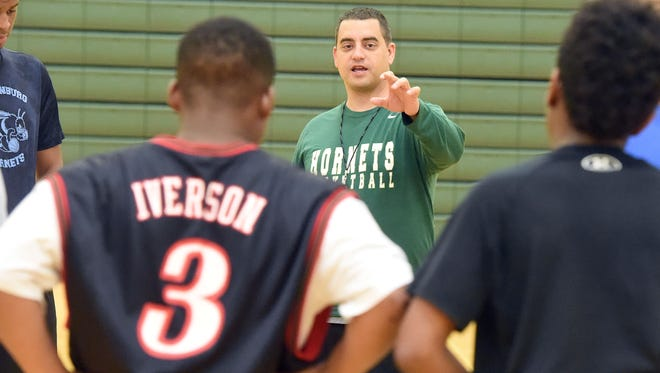 Coach Jeremy Hartman speaks with the athletes gathered to  practice their basketball skills during an open gym at Wilson Memorial High School on April 27, 2017. It was recently announced that Hartman will be taking over as head coach of the school's boys varsity basketball team.
