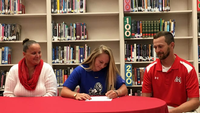 Madison Cash, center, signs her celebratory form for Eastern Mennonite University Tuesday. Madison will play softball for the Royals. Watching her are her mom, Misty Cash, and Riverheads softball coach Chad Coffey.