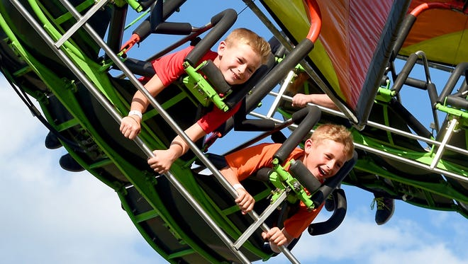 Two boys ride Cliff Hanger together on the midway at the Augusta County Fair on Thursday, Aug. 3, 2017.