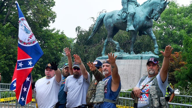 White nationalists offer a salute as they stand in front of the statue. Saturday's planned rally at Emancipation Park started early with fighting and devolved into bottle-throwing clashes between racist alt-right demonstrators who organized the event, white nationalists, neo-Nazis and counter protesters in Charlottesville.  Later during a counter march along Water Street near the Mall, a driver drove his car into a group of protesters, killing one.