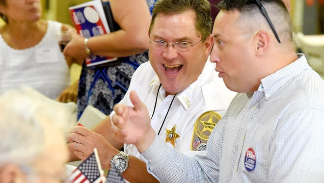 Matt Robertson, who is running for Staunton City Sheriff, shares a laugh with others he shares the table with at the event. The Greater Augusta Regional Chamber of Commerce hosted an event allowing people to mingle and dine with elected officials, called Pig PickingÕ & PolitickinÕ, at Augusta Expo on Monday, August 22, 2017.