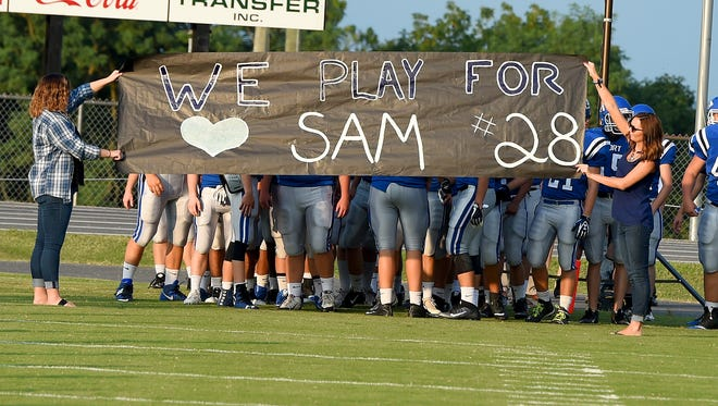 A banner honoring Fort Defiance's Sam Hill is stretched out for the team to run through before the start of a football game played in Fort Defiance on Friday, August 25, 2017. Hill was recently diagnosed with Wilson's disease.