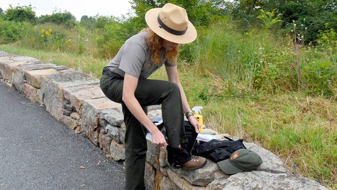 Park ranger Rebecca Unruh, a back country ranger with the National Park Service, demonstrates the proper way to wear a gaiter that can help protect against ticks.