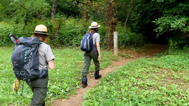Park ranger Rebecca Unruh of the National Park Service follows fellow ranger Sally Hurlbert along a hiking trail assessable from Hightop Mountain parking area on the Shenandoah National ParkÕs Skyline Drive on Aug. 23, 2017. Both wear hats and gaiters as well as have shirts tucked into pants and clothing treated to deter ticks.