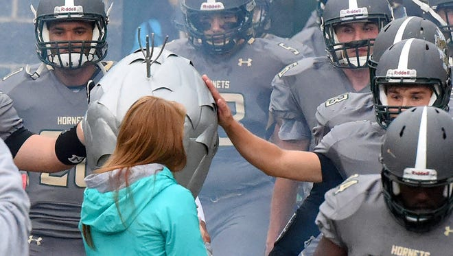 Players reach out to touch the hive that represents them as the Hornets of Wilson Memorial High School while making their way to the field to face Waynesboro High School in a football game played in Fishersville on Friday, Sept. 1, 2017.
