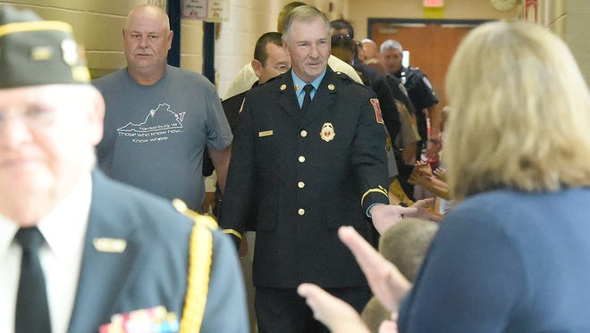 """First responders, active military and veterans walk through the halls of Clymore Elementary to the sound of applause coming from students and faculty gathered to either side of the hallway. Clymore Elementary held its annual """"National Anthem Day"""" on Sept. 11, 2017."""
